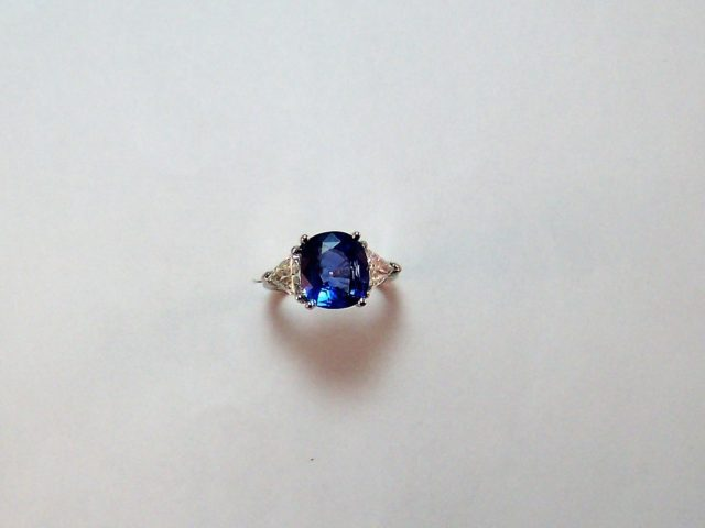 Platinum 4.50ct Oval Sapphire center ring with 1.50ct t.w. triangle diamond sides